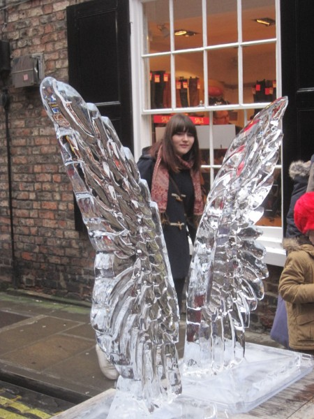 An innocent bystander peeps through the angel wings