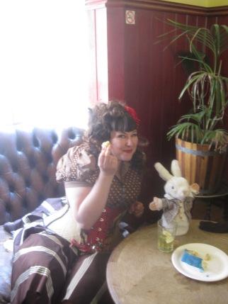 Jema eating cake, accompanied by Mr. Woppit