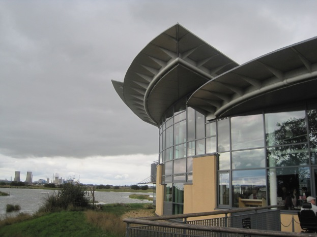 The modern windows of the visitor centre, industry on the horizon.