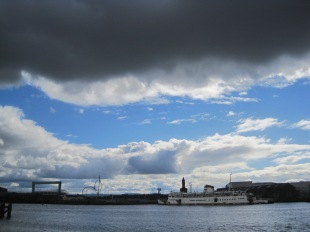 The darkening sky adds drama to the industry on the far shore.