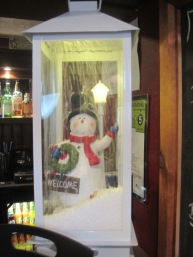 And on the bar, the jolliest snowman beams through falling snow.