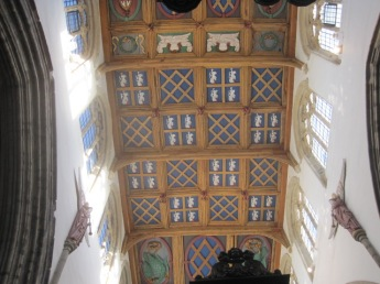 To the heraldic shields on the ceiling