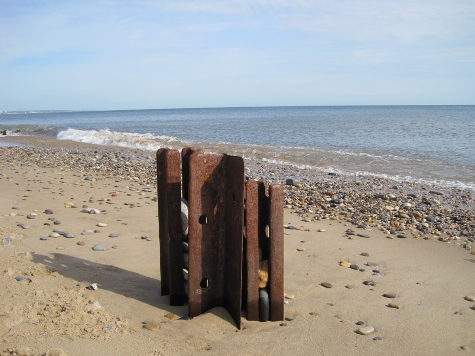 Rusted groynes litter the shore