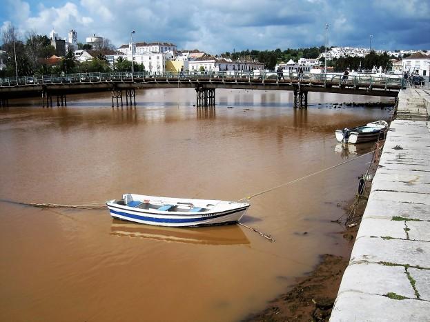 The river runs bronze after heavy rain